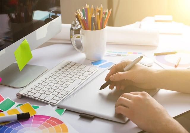 Un ordenador y unas manos con un bolígrafo simulando que está diseñando.