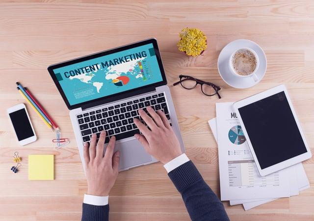 Un ordenador que pone en la pantalla content marketing y unas manos tecleando en el mismo ordenador.